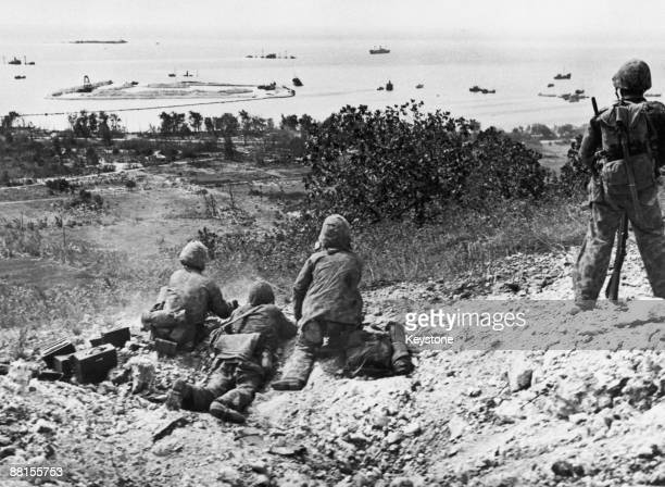 An American Marine machine gun crew firing on Japanese forces from a hill overlooking Tanapag harbour during the Battle of Saipan in the Northern...