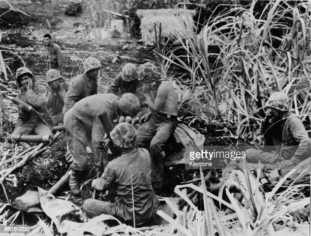 An American Marine mortar crew in a cane field on Saipan Island during the Battle of Saipan in the Northern Mariana Islands, 30th June 1944.