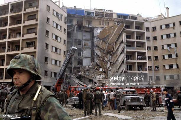 An American Marine Second Lieutenant stands with his back to rescue workers swarming the ruins of the American embassy after a suicide bomber...