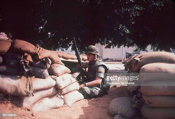An American Marine sits with his rifle behind a sandbag position after the suicide bombing that destroyed the American barracks and killed 241...