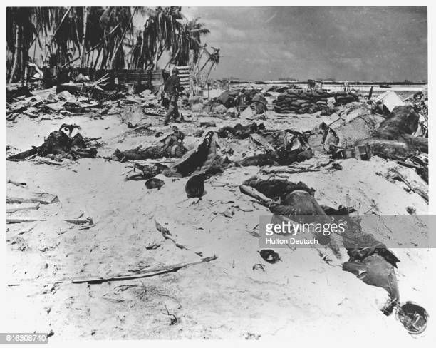 An American marine walks past the bodies of dead Japanese soldiers lying across the sands of Tarawa in the Pacific