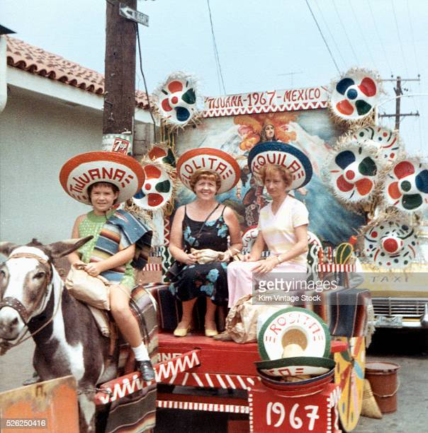 An American mother and her two daughters ride in a donkey drawntourist cart in 1967