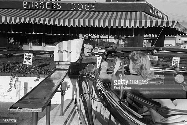 An American motorist stops at a drivethrough burger joint in Hollywood California Original Publication Picture Post 5298 We Go To Hollywood pub 1951