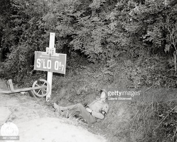 An American MP is resting next to a signpost of Saint-Lô. It is the Military Police Sergeant Rex Potts of the 29th U.S Infantry Division. The exact...