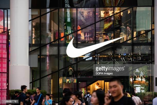 An American multinational sportswear corporation Nike logo seen in Shanghai with pedestrians walking past it.