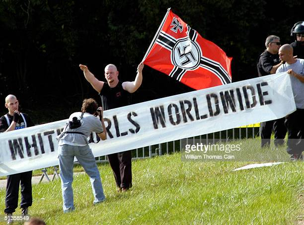 An American Nazi party member waves a flag as another member makes a picture during American Nazi Party rally at Valley Forge National Park September...