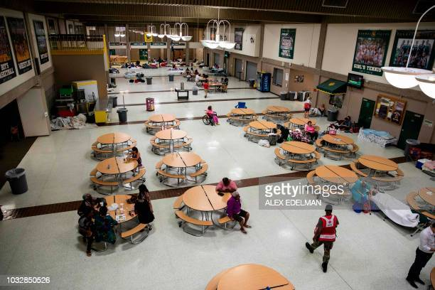 An American Red Cross aid worker walks through the cafeteria at Conway High School which is being used as a Hurricane Florence evacuation shelter at...