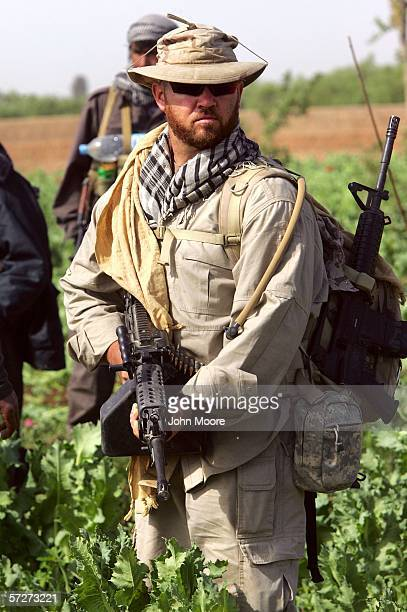 An American security contractor for DynCorp walks through an opium poppy field on April 3, 2006 near Lashkar Gah in Helmand province of southern...