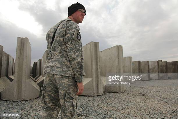 An American serviceman inspects hundreds of concrete barriers at Forward Operating Base Howz-e-Madad, in Kandahar Province, March 1, 2011. The...