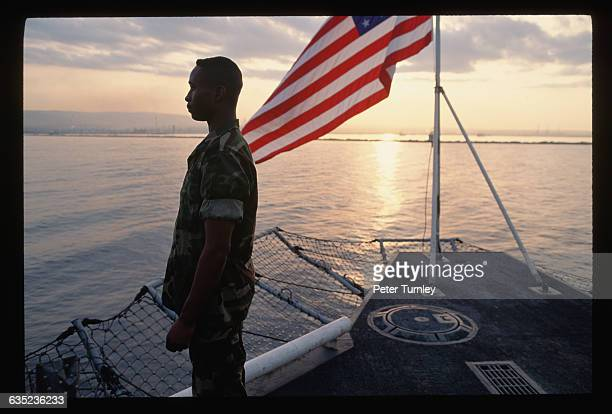 An American serviceman stands on the deck of the USS Saipan aircraft carrier and stares out into Augusta Bay He is part of an American peacekeeping...