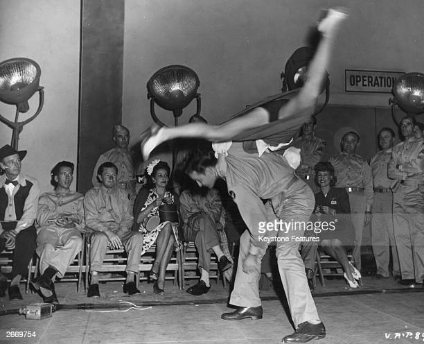 An American serviceman throwing his jitterbug dance partner over his back
