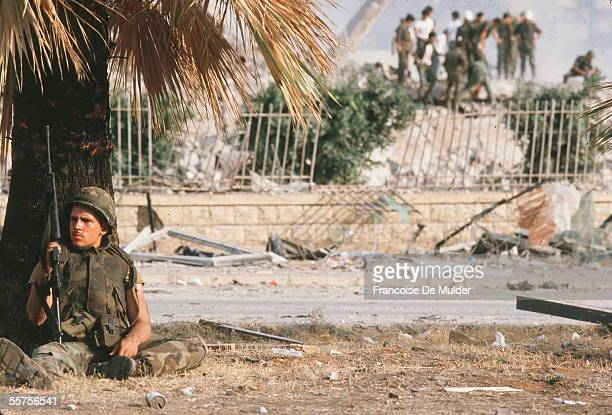 An American sits under a palm tree with his M16 as in the background comrades inspect the damage after the suicide bombing that destroyed the...