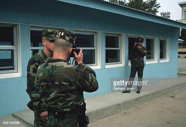 An American soldier and a North Korean soldier photograph one another in Panmunjom on the 38th parallel in the DMZ or demilitarised zone This 25 mile...