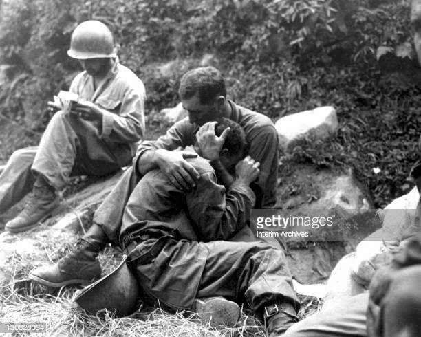 An American soldier comforts a fellow infantryman whose close friend has been killed in action, Haktong-ni area, Korea, August 1950. A corpsman fills...