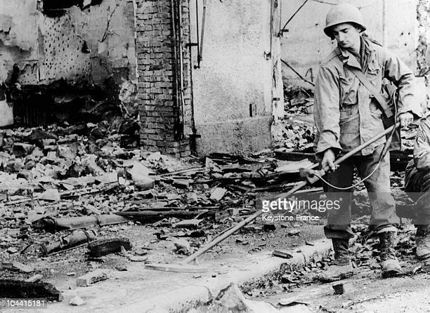 An American soldier equiped with a landmine detector working in the streets of a town in Vosges at the time of the liberation during the fall of 1944