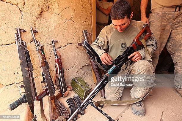 An American soldier from Charlie Company the US Army's 10th Mountain Division inspects weapons recovered from a firefight with Taliban forces near...