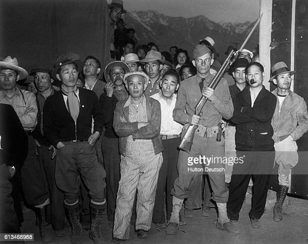 An American soldier guarding a crowd of Japanese American internees at an internment camp at Manzanar California USA during World War II | Location...