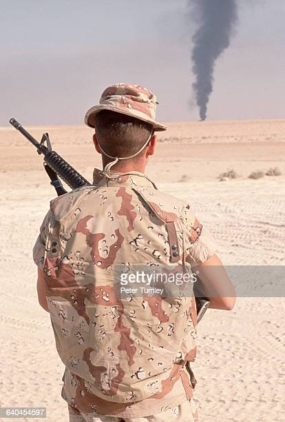 An American soldier in a northern Kuwaiti desert near the Iraqi border watches a dark plume of smoke rise from the horizon He is part of a USled...