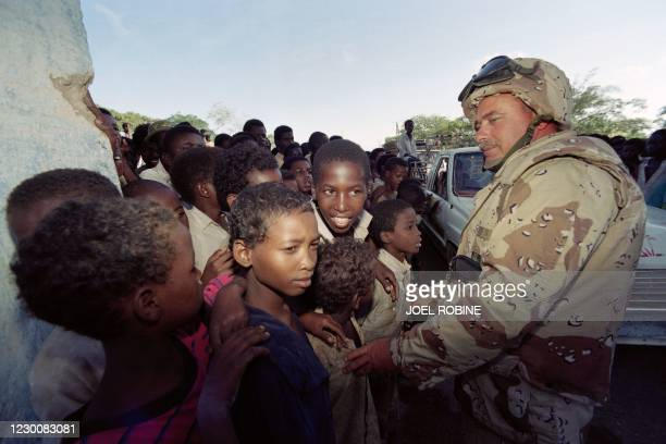 "An American soldier meets Somali children on December 14, 1992 at Baidoa as part of the ""Restore Hope"" military operation. - On December 3 the UN..."