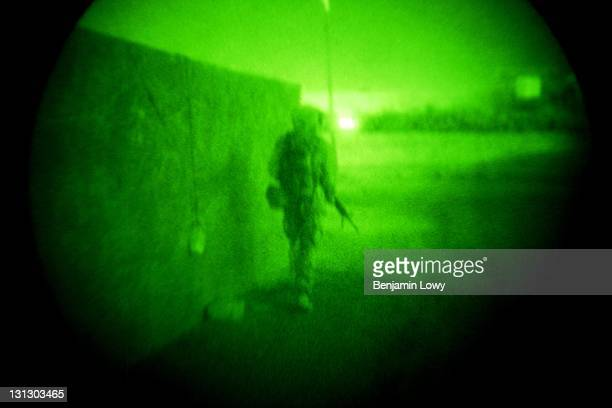 An American soldier peaks around the corner of a wall during an exfiltration from an American sniper position on August 7 2003 in Tikrit Iraq A three...