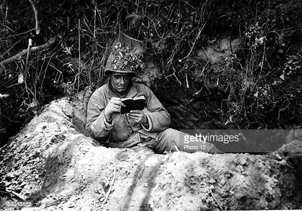 An American soldier reads his prayer book in a foxhole near the front lines in the St Lo sector in France