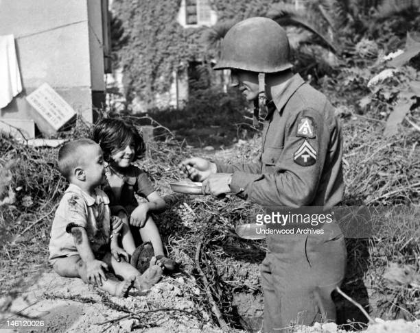 An American soldier shares his rations with two hungry Italian waifs, Italy, October 6, 1943.