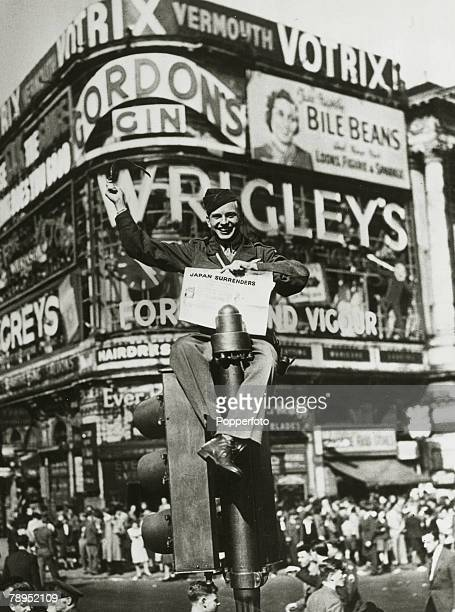 An American soldier sits on top of a traffic light in Piccadilly Circus during Victory over Japan Day celebrations to mark the end of conflict in...