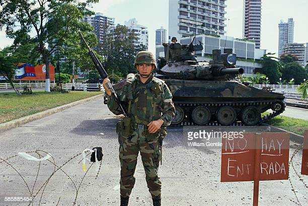 An American soldier stands guard at a roadblock near a Catholic archdiocese where Panamanian strongman Manuel Noriega is hiding