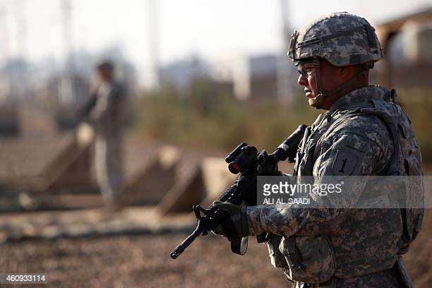 An American soldier stands guard at the Taji base complex which hosts Iraqi and US troops and is located thirty kilometres north of the capital...
