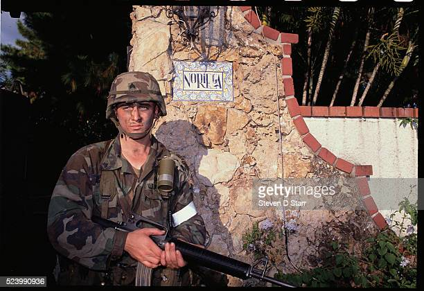 An American soldier stands guard outside the home of Panamian leader Manuel Noriega. The United States invaded Panama in 1989 to bring Noriega back...