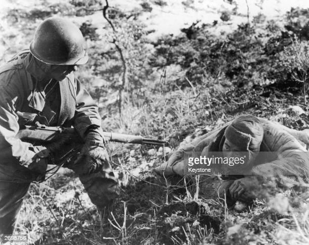 An American soldier taking a communist prisoner during the Korean war
