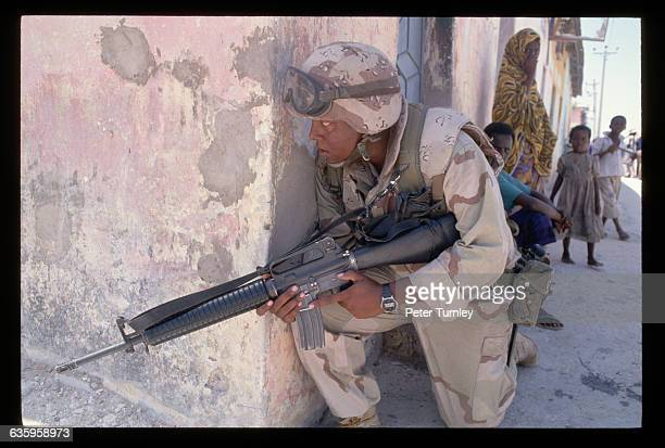 An American soldier warily peers around the corner of a building while a Somali woman and children watch In the 1980s civil war erupted in Somalia...