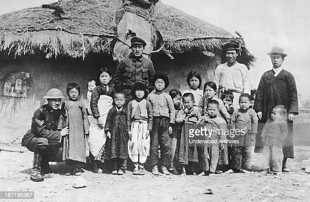 An American soldier with a Chinese family in Siberia, Vladivostok, Siberia, Russia, August 21, 1919. The American troops are there fighting the...