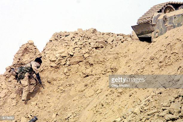 An American special operation soldier climbs a hill during fighting against proTaliban forces November 27 2001 in a fortress near MazareSharif...