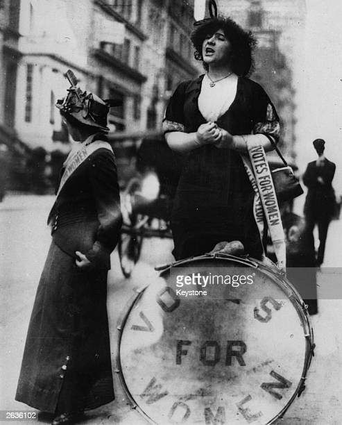An American suffragette giving a speech in the street She is standing behind a drum bearing the slogan 'Votes For Women'