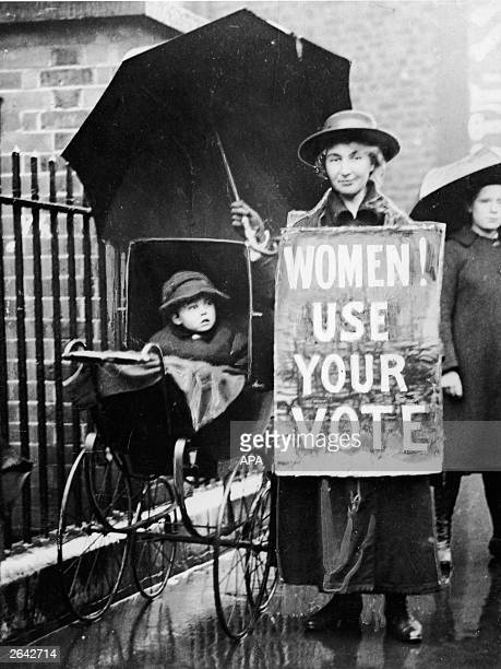 An American suffragette with an umbrella stands next to a baby carriage and wears a sign proclaiming 'Women Use your vote' circa 1920