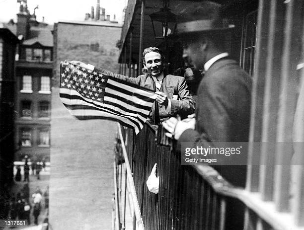 An American sympathizer waves a flag behind Bow Street Court, London, during the trial of a group of suffragettes, circa 1913. June 14, 2001 is Flag...