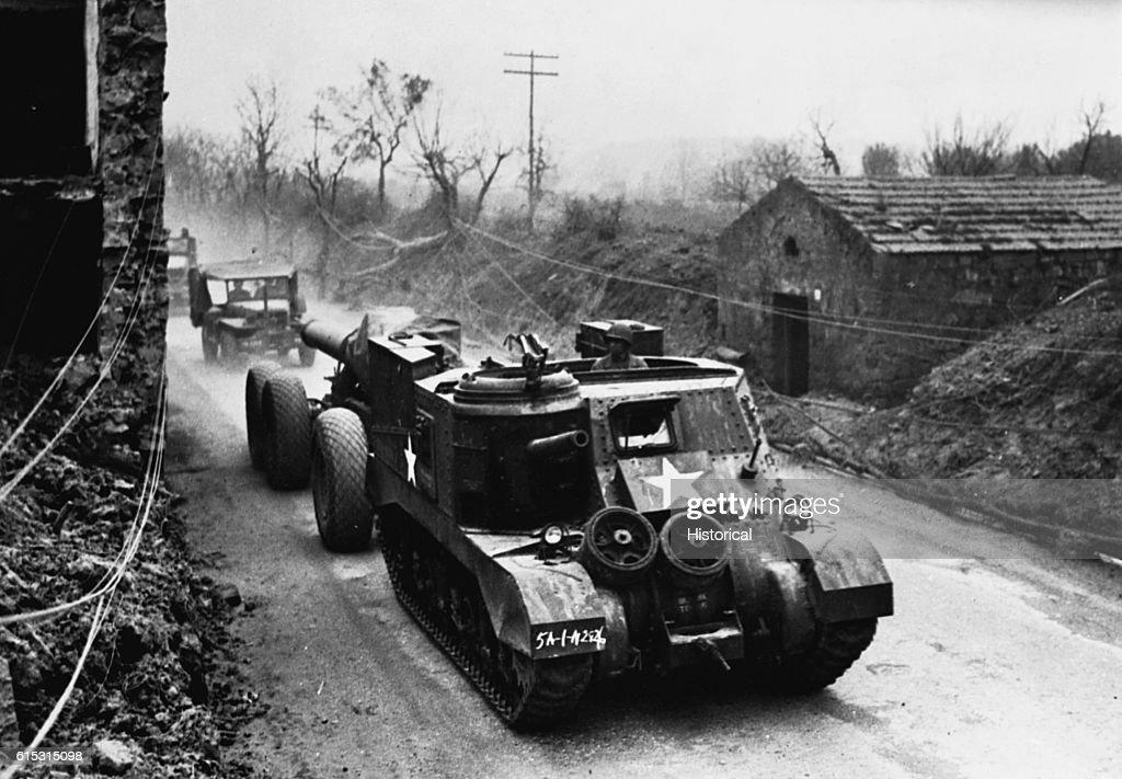 An American tank pulls a 240mm Howitzer gun down a road