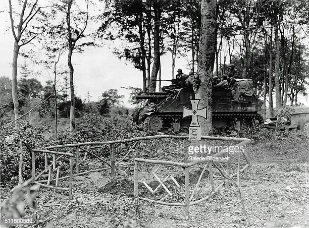 An American tank with several soldiers atop is standing in the forest. July 1944. In front of it is the grave of SS Unterscharführer Josef Richtsfeld...