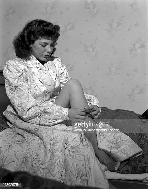 An American young woman portrayed while taking off her tights sitting on her bed Lausanne 4th January 1949