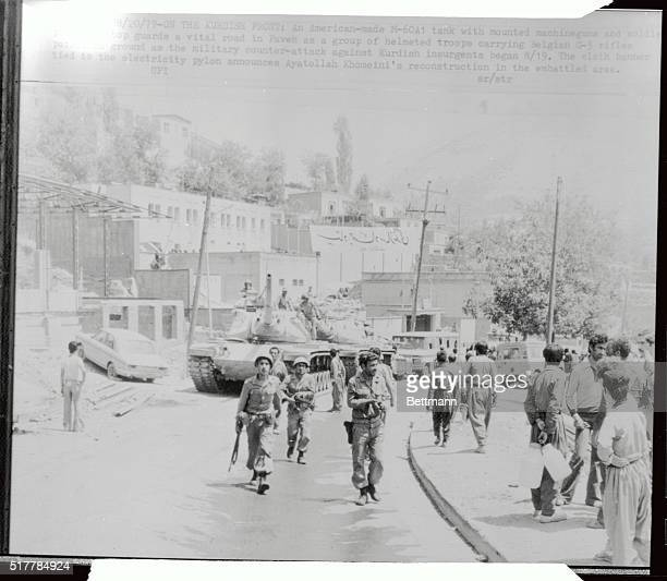 An Americanmade M60A1 tank with mounted machine guns and soldiers posted on top guards a vital road in Paveh as a group of helmeted troops carrying...