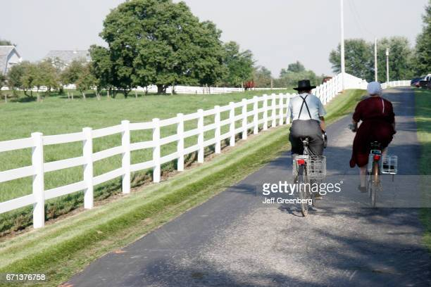 An Amish couple riding bicycles on a country lane in Shipshewana