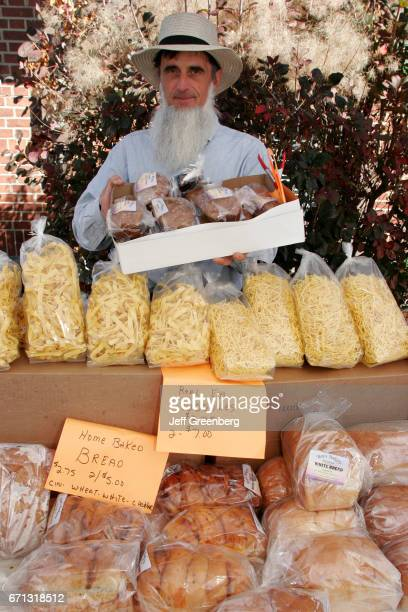 An Amish man selling home baked bread and noodles at the European Market on Broadway Avenue