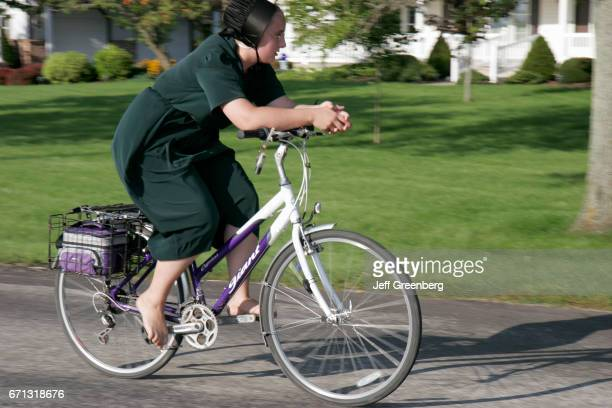An Amish teen girl riding a bicycle barefoot