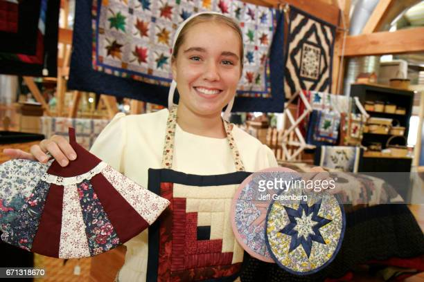 An Amish teen girl selling quilt potholders at American Countryside Farmers Market