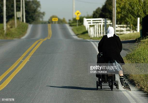 An Amish woman uses inline skates to push a baby carriage 07 October near BirdinHand Pennsylvania Amish are descendants of SwissGerman Mennonites who...