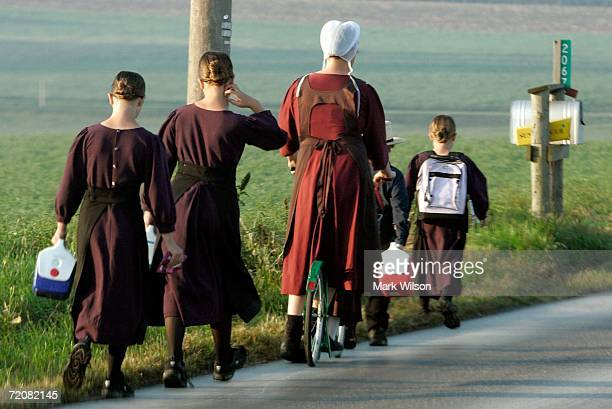 An Amish women escorts young children to school near the one room Amish schoolhouse where the shooting took place two days prior October 4 2006 in...