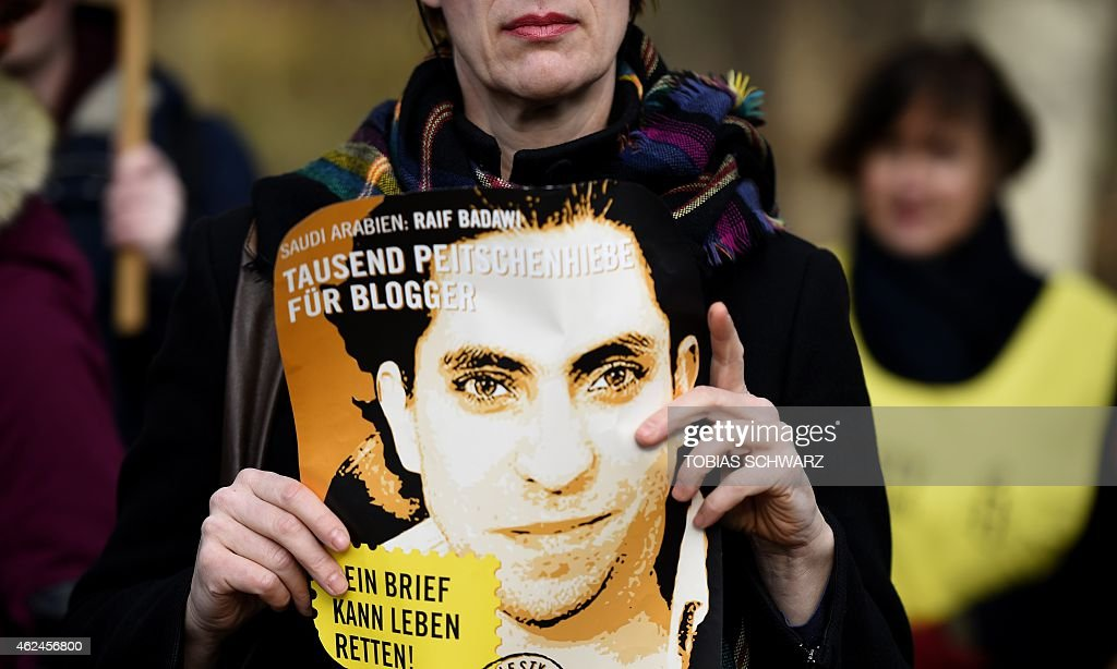 An Amnesty International activist holds a picture of Saudi blogger Raif Badawi during a protest against his flogging punishment on January 29, 2015 in front of Saudi Arabia's embassy to Germany in Berlin. The 30-year-old Saudi has been sentenced to 1,000 lashes for insulting Islam and is serving a 10-year jail term - a case which has drawn widespread international criticism.