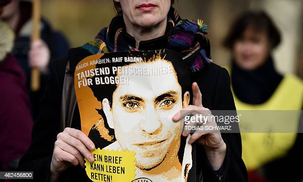 An Amnesty International activist holds a picture of Saudi blogger Raif Badawi during a protest against his flogging punishment on January 29 2015 in...