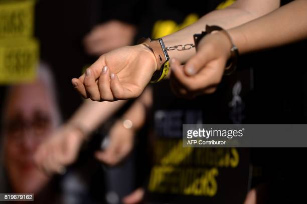 An Amnesty International activist wears handcuffs during a protest against the arrest of rights activists in Turkey including Amnesty International's...
